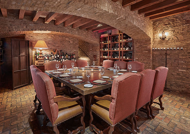 inset-Wine cellar with wooden table & chairs