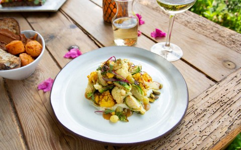 vegetable dish on table with wine