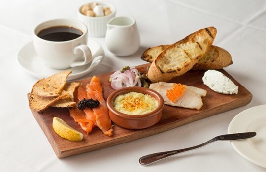 Assortment of breakfast items on a wood plate and a cup of coffee