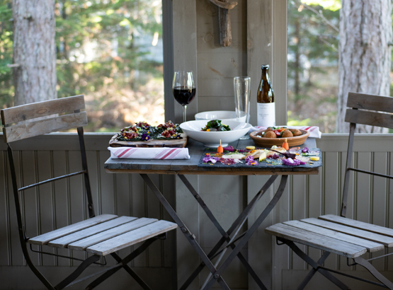 two chairs and a table on a porch with dinner set up and some red wine