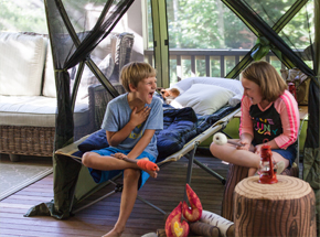 two kids laughing in a tent pitched on their porch