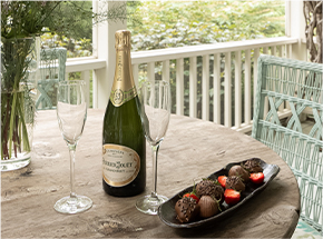 bottle of champagne with two champagne flutes and chocolate covered strawberries