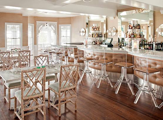 dining tables in restaurant with bar that also has seating