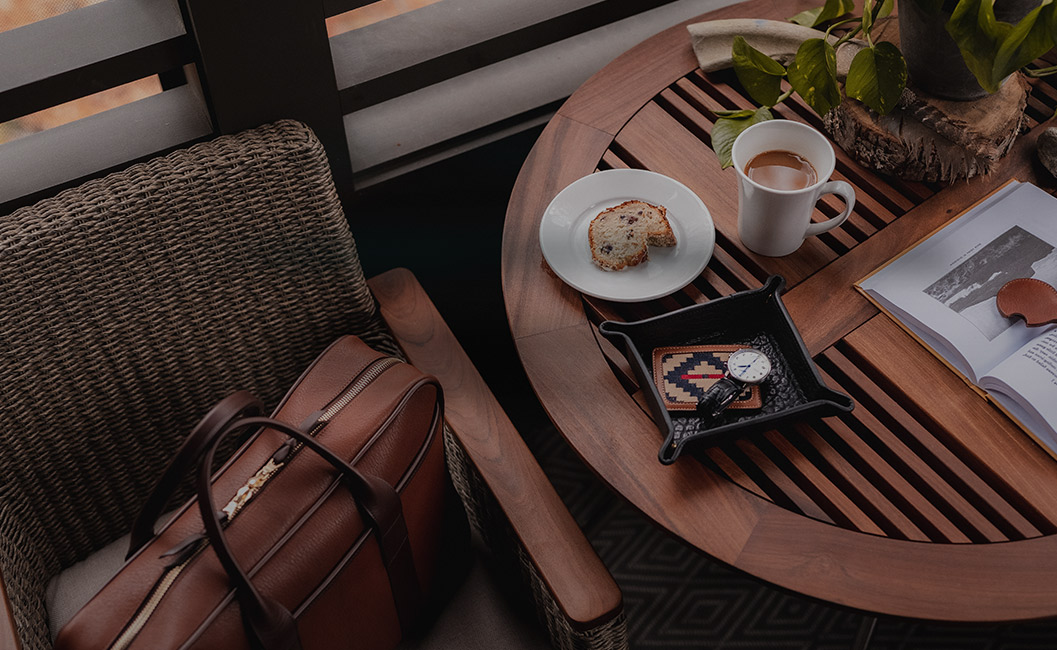 table with bread on a plate and a cup of coffee with a carryon bag in the chair next to it