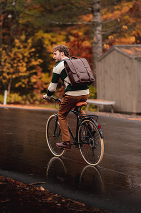 man wearing a backpack and riding a bicycle outside