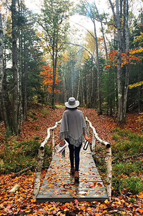 woman walking over a bridge outside wearing a hat and poncho with colorful leaves on the ground