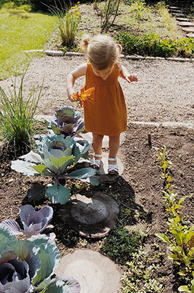 child standing in the garden outside holding flowers and looking down