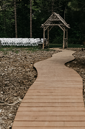 wooden pathway leading to alter at an outdoor wedding ceremony