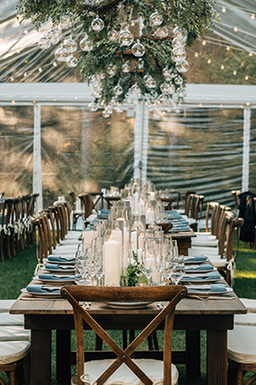 long table set inside a tent for a wedding reception