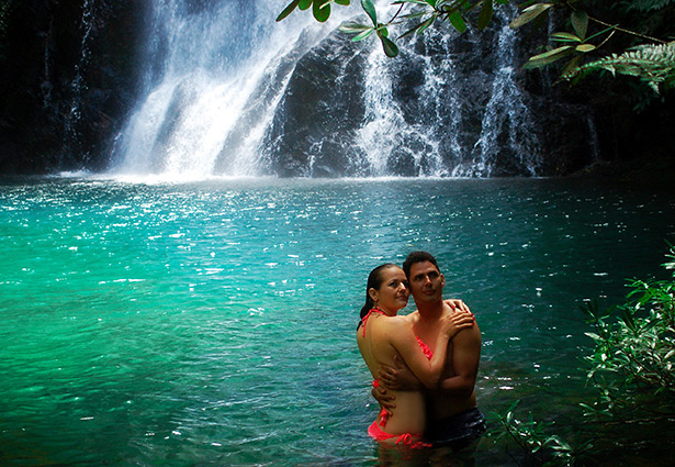 a couple hugging in the water with the waterfall in the background