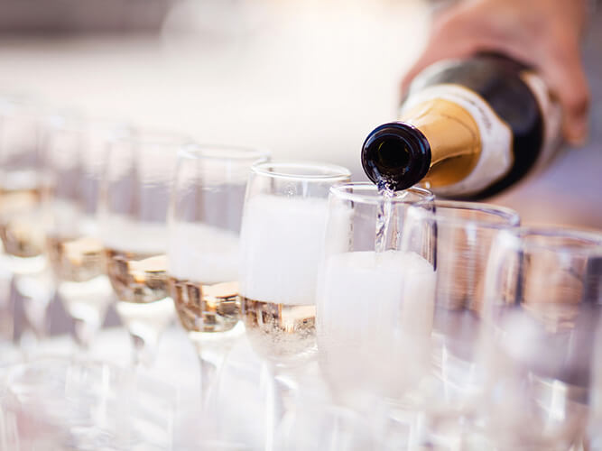 Close up of champagne being poured into flute glasses