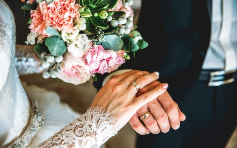 image of a bride and groom holding hands with a bouquet