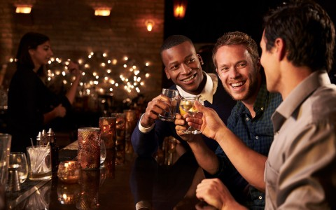 Group of 3 men having drinks at a bar