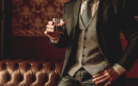 Close up of man in suit holding glass of alcohol