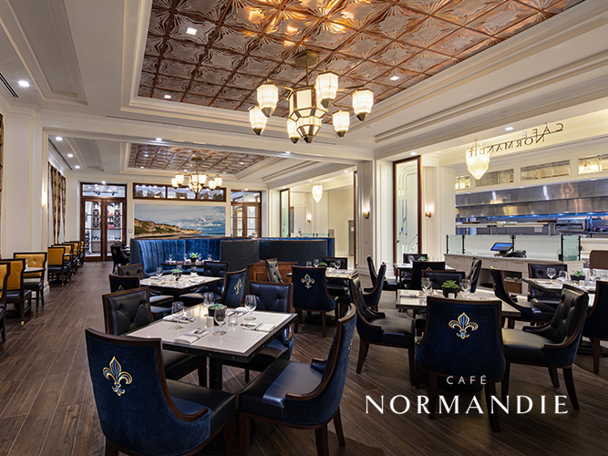 dining room with blue chairs and cafe normandie logo
