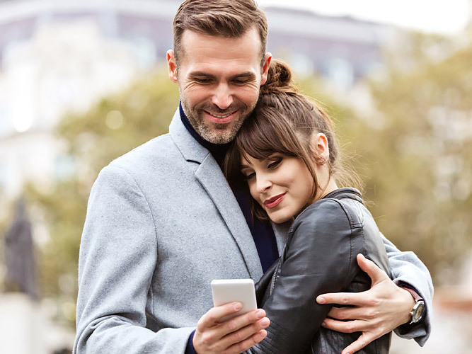 man and wife hugging outside with a cellphone