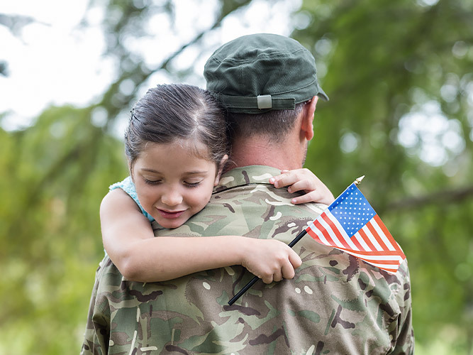 little girl hugging a marine with american flag in hand
