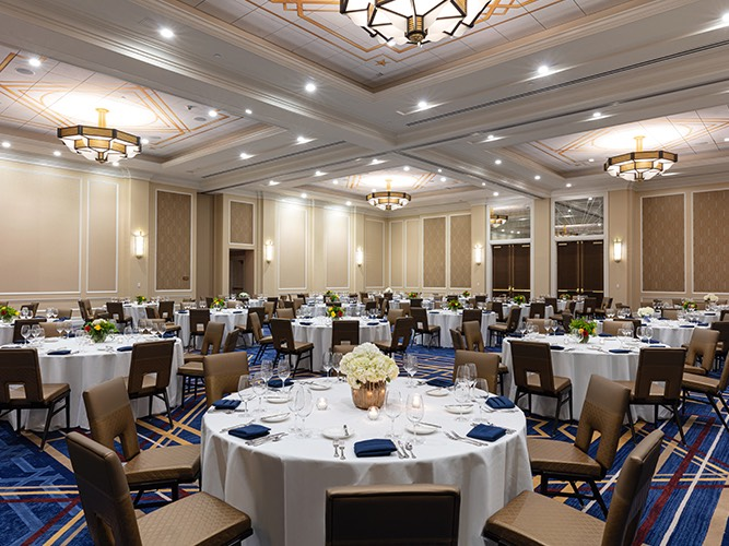large round tables with white cloth and blue chairs
