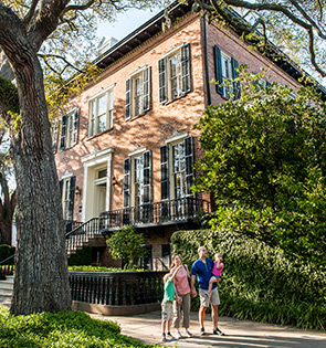 family posing outside historic savannah home taking a photo