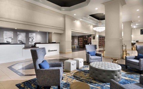 lobby seating area adjacent from reception desk with its large wing backed chairs, tufted coffee table and continued grey and navy color scheme
