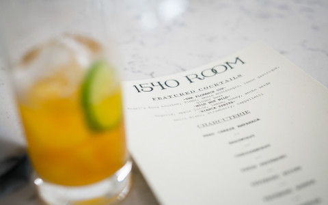 an orange cocktail with a lime in it next to a 1540 room menu