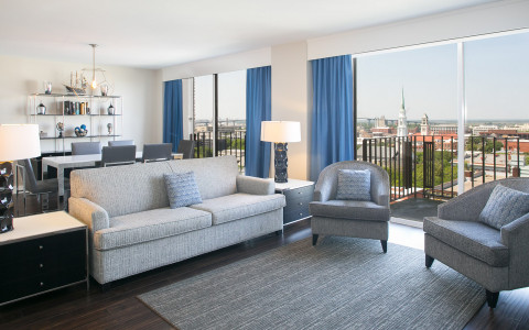 guestroom with a seating area and dining area overlooking the city