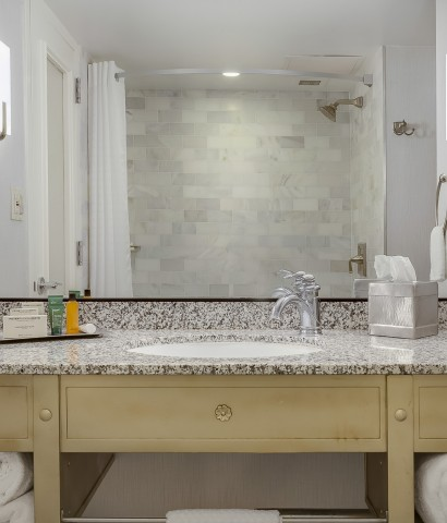 bathroom vanity has single sink a toped with toiletries. Large mirror framed by sconces