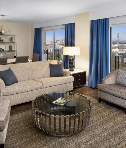 suite living room. Dining table and living room seating area lead to 2 sliding glass doors to balcony with city views