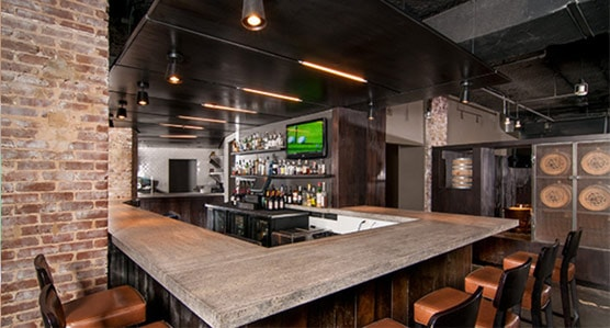 on site dining interior has a speakeasy concept with brick walls. Large bar faces wall of spiritis and tv.