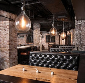 on site dining interior has a speakeasy concept with brick walls, black leather tufter booths and edison bulbs lighting