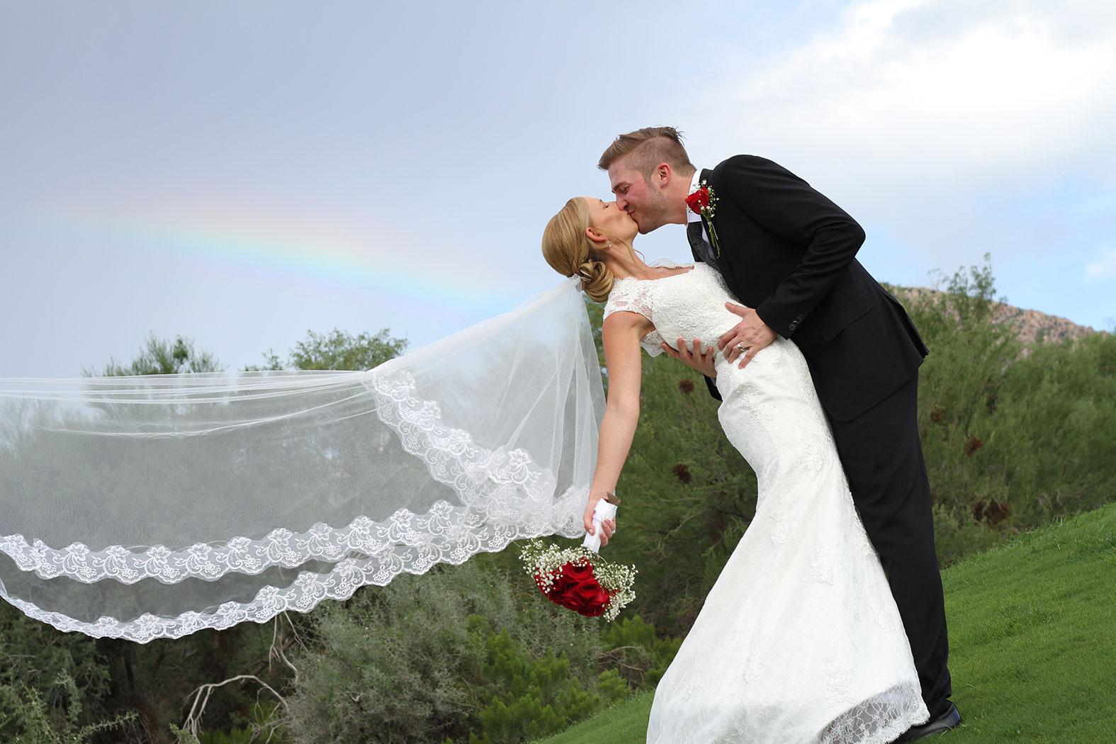 groom kissing bride outside with a rainbow in the background