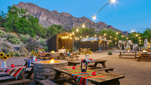 tables and chairs outside with a fire pit and string lights and the desert landscape in the background