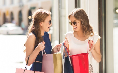 women holding shopping bags and talking
