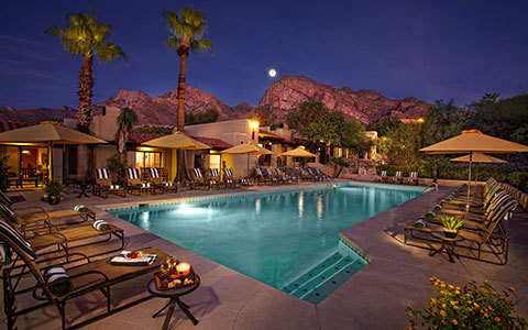 Pool at night with palm trees and cabanas