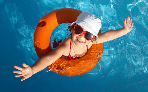 little girl in the pool with a flotation device