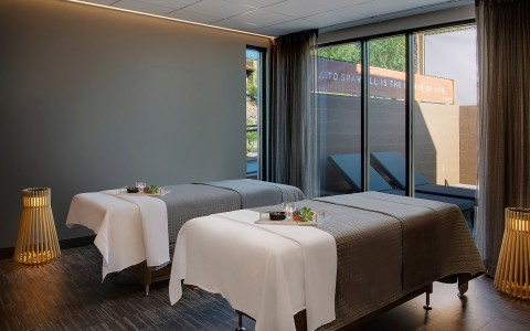 two spa beds in spa room with window in background