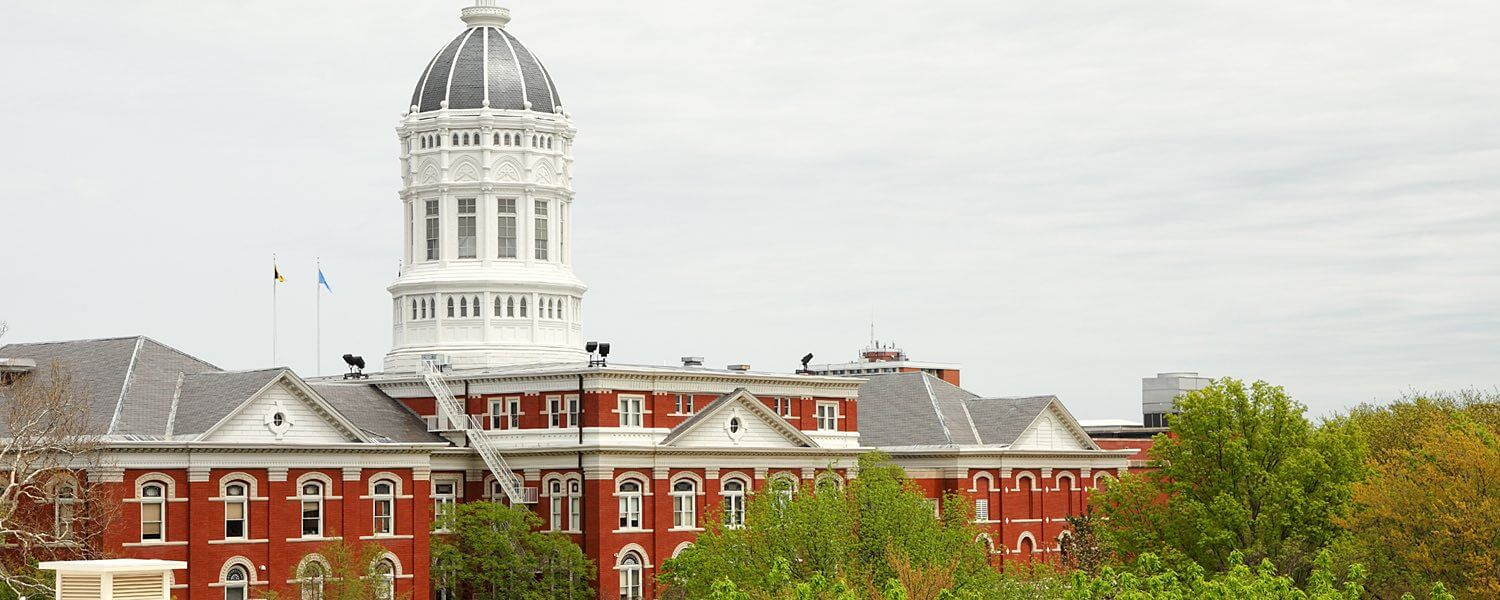 A large red and white university building with a dome steeple