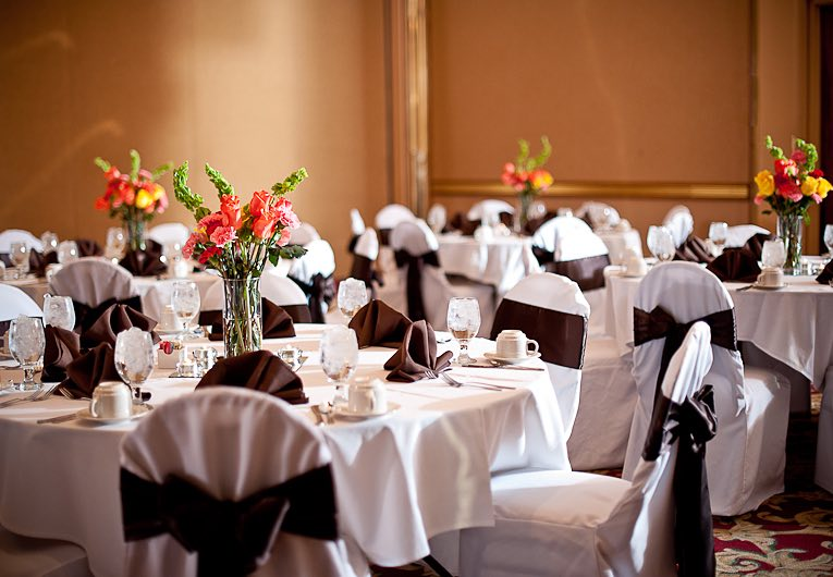 tables set for an event decorated with flower centerpieces