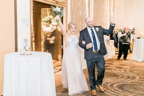 bride and groom celebrating walking into the reception area