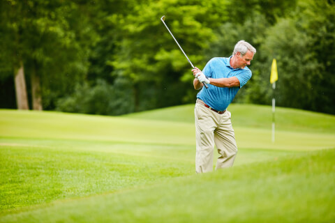 A man swings a golf club on the golf course