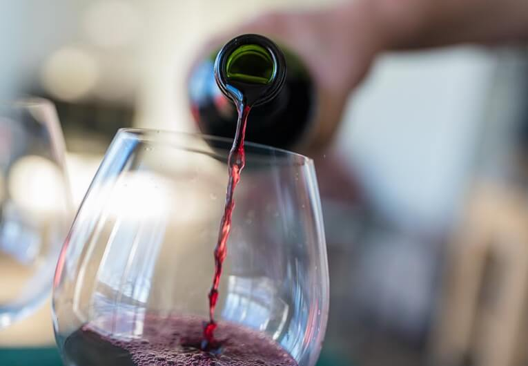 someone pouring red wine into a glass