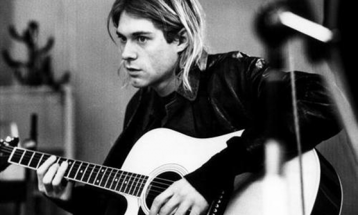 Black and White Photo of Kurt Cobain Holding a Guitar