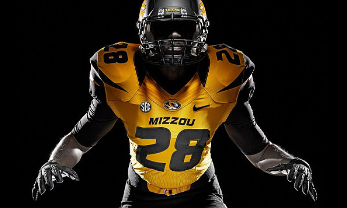 MIZZOU football player in gold jersey number 28 against a black background