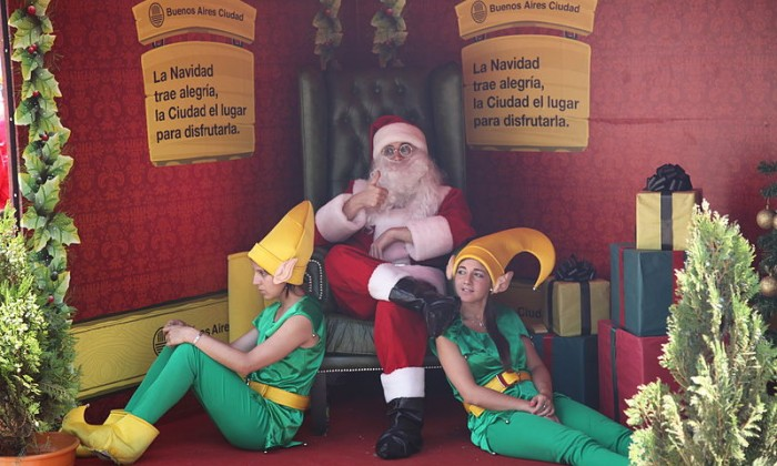 Santa sitting on a chair with two elves sitting on the floor in front of him
