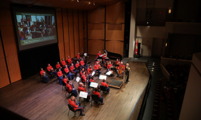 Small Orchestra performing in front of a screen in red uniforms