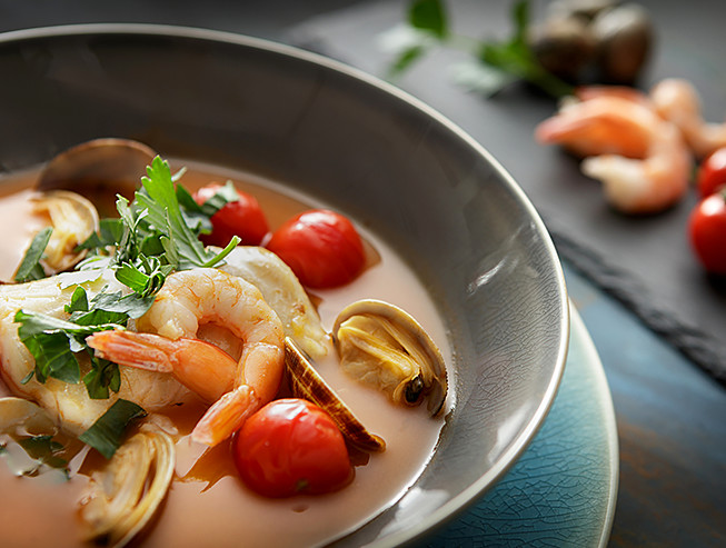 Close up of soup with clams, cherry tomatoes & shrimp