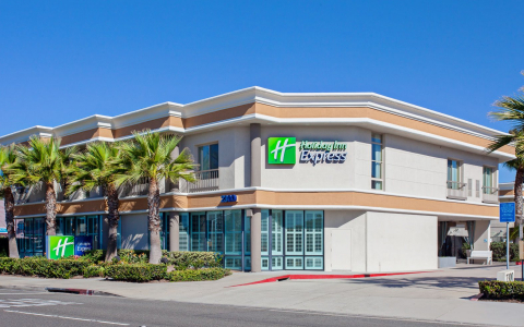 Holiday Inn Express sign on building with palm trees next to it
