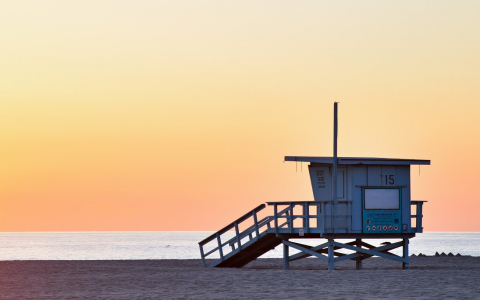 Lifeguard shack on sand with sun setting in the back