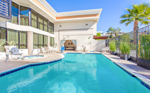 Property pool with jacuzzi & white loungers