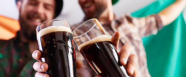 Two men in plaid shirts toasting with dark beer